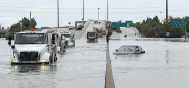 A man walks down the median as trucks navigate floodwaters from Tropical Storm Harvey along Interstate 610 Sunday, Aug. 27, 2017, in Houston, Texas.