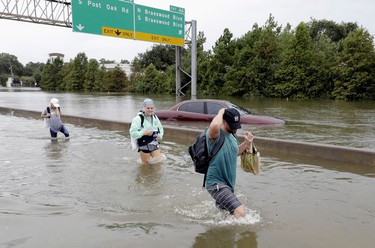 Evacuees wade down a flooded section of Interstate 610 as floodwaters from Tropical Storm Harvey rise Sunday, Aug. 27, 2017, in Houston, Texas.