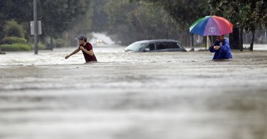 Moses Juarez, left, and Anselmo Padilla wade through floodwaters from Tropical Storm Harvey on Sunday, Aug. 27, 2017, in Houston, Texas.