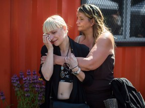 FILE PHOTO - A woman is consoled while wiping away tears during a memorial service to remember those who have died in the province as a result of the drug overdose crisis, on International Overdose Awareness Day in the Downtown Eastside of Vancouver, B.C., on Thursday August 31, 2017.