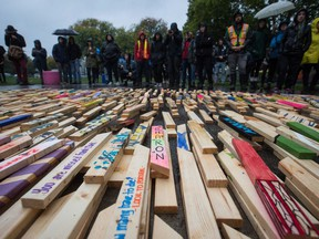 People listen to speeches on Sept. 29, 2017, as 2,224 wooden stakes representing the number of confirmed overdose deaths in B.C. over the last three years, many of them painted with names of overdose victims, are placed on the ground at Oppenheimer Park in Vancouver.