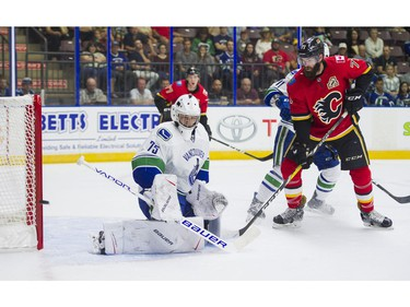 Vancouver Canucks goalie Michael DiPietro (left) makes a save and deflects the puck wide of the net as Calgary Flames Hunter Smith looks on during NHL preseason hockey Sunday, September 10