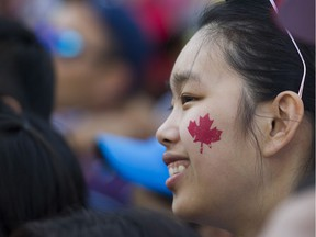 """Census shows Caucasians are the """"visible minority"""" in Richmond, Surrey, Burnaby, Coquitlam and the city of Vancouver. as well as Greater Toronto. (PHOTO - A woman sports a maple leaf at the Canada Day celebrations at Canada Place, Vancouver."""