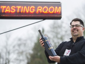 Jason Ocenas, manager of Township 7 Vineyards & Winery in Langley, holds a bottle of wine at the Langley tasting room.