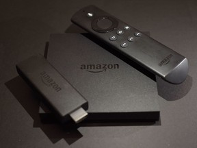 This November 2016 photo shows the Amazon Fire TV, centre, and Fire TV Stick, left, streaming television devices in New York.