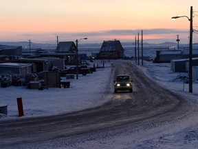 The sun rises as a car drives along a road in Iqaluit, Nunavut on Wednesday, December 10, 2014.