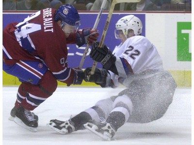 Jan. 3, 2002: Canucks' left winger Daniel Sedin (22) is knocked down by Montreal Canadiens' center Yanic Perreault (94) during first period.