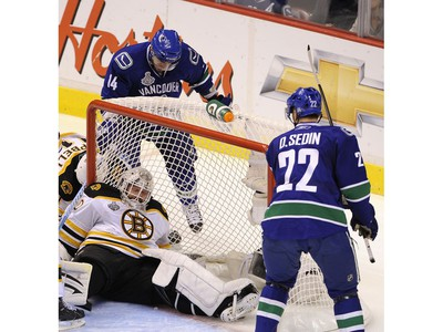 JUNE 16, 2011 --  Alexandre Burrows and Daniel Sedin of the Vancouver Canucks look on as goalie Tim Thomas of the Boston Bruins sits on the puck