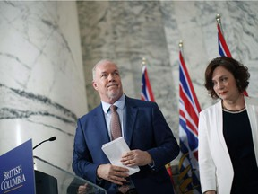 Minister of Energy Michelle Mungall, with Premier John Horgan, was less then thrilled to learn of a $100-million loss for B.C. Hydro in a contract dispute over construction of a major transmission line.