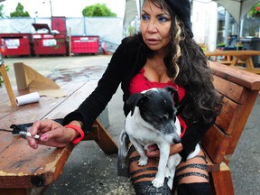 Mona Woodward holds her dog Tina at a free animal health-care clinic in Surrey.