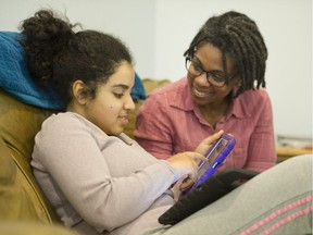 Nicole Kaler with her 17-year-old autistic daughter Maya as she uses two iPads. Maya is non-verbal and has high needs.