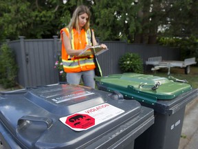 Julie Kanya, the urban wildlife coordinator for the City of Coquitlam, inspects garbage and recycling carts on the street.