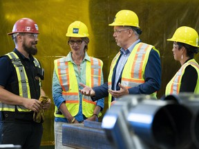 B.C. Premier John Horgan (centre) Minister of Advanced Education Melanie Mark (right) and Minister of Transport Claire Trevena during a tour of the ironworkers training facility at BCIT in Burnaby, BC, July, 16, 2018.