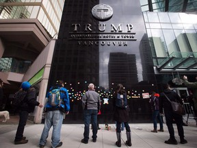 File: People look at written messages posted on the building outside the official opening of the Trump International Hotel and Tower in Vancouver, B.C., on Tuesday February 28, 2017.