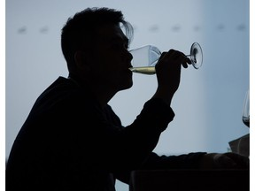 A visitor drinks a glass of wine during a tasting event at Vinexpo in Hong Kong on May 24, 2016.