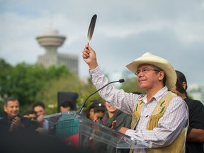 Lee Spahan, chief of the Coldwater Indian Band, raises an eagle feather in celebration in Vancouver on Thursday, after the Federal Court of Appeal's decision to quash approval of the Trans Mountain oil pipeline expansion.
