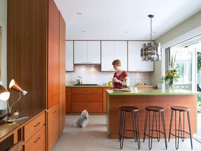 Home owner Joelle Bradley and her dog Mae love the breezy galley kitchen reno with its easy access through Nano doors to the outside terrace. The original '60s chandelier over the avocado quartz and cherrywood island is made of smoked acrylic plastic circles. It's one of several original vintage lighting fixtures discovered in the house.