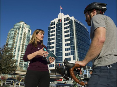 Candidate for mayor of Vancouver Shauna Sylvester talks with a cyclist as she campaigns at Quebec and Terminal on Oct. 19, 2018.
