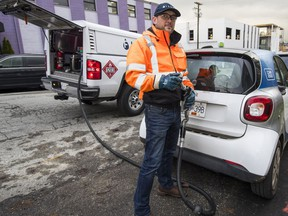 Dustin Ellis of Filld prepares to fuel up a Car2Go vehicle. The company is now offering its service to the public.