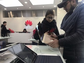 Foreigners look at a Huawei computer at a Huawei store in Beijing.