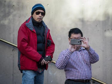 A man takes a photograph with a smartphone while waiting in line to enter a courtroom to attend a bail hearing for Meng Wanzhou, the chief financial officer of Huawei Technologies, at B.C. Supreme Court in Vancouver, on Dec. 7, 2018.