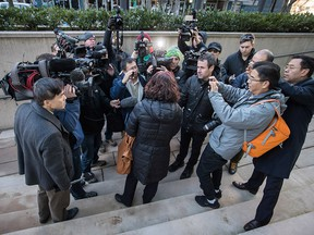Members of the media crowd around an unidentified woman who was attending a bail hearing for Meng Wanzhou, the chief financial officer of Huawei Technologies, during a break in proceedings at B.C. Supreme Court in Vancouver, on Friday December 7, 2018. She was arrested Saturday after an extradition request from the United States while in transit at the city's airport.