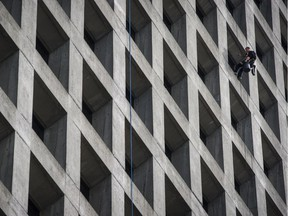 A window washer dangles outside office tower at 1075 West Georgia in Vancouver in this 2016 file photo.