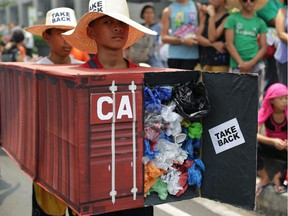 Filipino environmental activists wear a mock container filled with garbage to symbolize the 103 containers of waste that were shipped from Canada to the Philippines in 2013. The president of the Philippines says if Canada doesn't take back its trash, he will 'declare war' and ship the containers back himself.