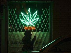 A pedestrian walks  past the Weeds neon sign on Burrard Street, Vancouver, in 2014.
