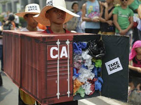 Filipino environmental activists on May 7, 2015 wear a mock container vans filled with garbage to symbolize the 50 containers of waste that were shipped from Canada to the Philippines two years ago, as they hold a protest outside the Canadian embassy at the financial district of Makati, south of Manila, Philippines.