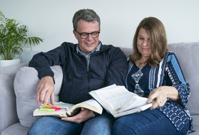 Kevin and Julia Garratt flip through the Bibles they had while jailed in China.