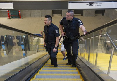 Transit Police Sgt. Clint Hampton and Const. Darren Chua ride the escalators to the platform at the Surrey Central Skytrain station.