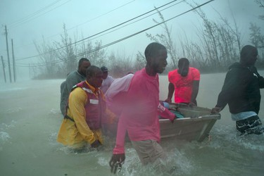 Volunteers rescue several families from the rising waters of Hurricane Dorian, near the Causarina bridge in Freeport, Grand Bahama, Bahamas, Tuesday, Sept. 3, 2019. The storm's punishing winds and muddy brown floodwaters devastated thousands of homes, crippled hospitals and trapped people in attics.