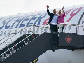 Conservative Leader Andrew Scheer and his wife Jill waves as they board the campaign plane in Ottawa earlier this month.