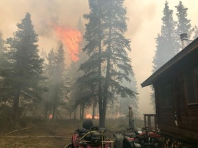 Firefighters from the Chugach National Forest work to protect the Romig Cabin on Juneau Lake from the Swan Lake Fire near Cooper Landing, Alaska, U.S. in this August 28, 2019 handout photo.