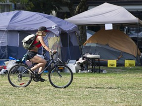 A cyclist rides through open space, and near tents, in East Vancouver's Oppenheimer Park in early September.