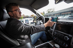 Lawyer Jerry Steele with a smart phone attached to the dash of his truck explains cellphone rules and recent court decision.