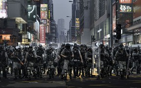 "Rémy Soubanère photo of police in Hong Kong on October 1st, 2019, the 70th anniversary of the People's Republic of China. It was declared ""grief day"" by protesters. The photo is part of an exhibition called Revolution of Our Times at the Polygon Gallery."