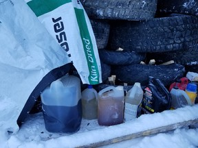 Jugs of accelerants and kindling under a stack of tires in a photo from the RCMP.