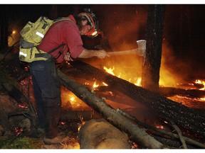 Forest Service fire fighters work in the pitch black night putting out hot spots.