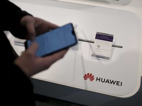 An employee demonstrates a Huawei smartphone at a Telus Corp. store in Toronto. Telus says it will launch a 5G network in Canada this year using Huawei equipment.