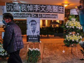 People wearing masks attend a vigil for the late Dr. Li Wenliang, an ophthalmologist who died of coronavirus at a hospital in Wuhan, in Hong Kong, China on Feb. 7, 2020.