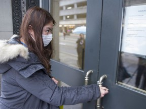 A student tries to enter University Canada West in Vancouver on  Thursday. The school is closing for three days for disinfection after two students were potentially exposed to the new coronavirus.