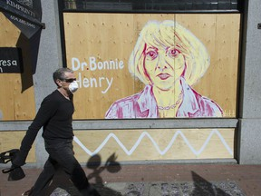 A man walks past a painted COVID-19 mural of Dr. Bonnie Henry on Tuesday along Powell Street in Vancouver.
