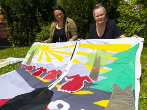 Ursula Andrade and Kaytee Kilgour with the arpilleras that are being installed Saturday outside St. Andrew's-Wesley United Church.