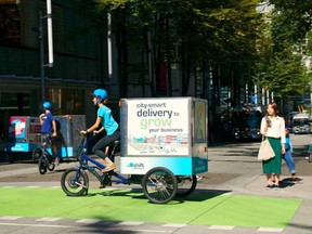 A delivery person is pictured riding a cargo e-bike in downtown Vancouver, B.C. in this undated handout photo.
