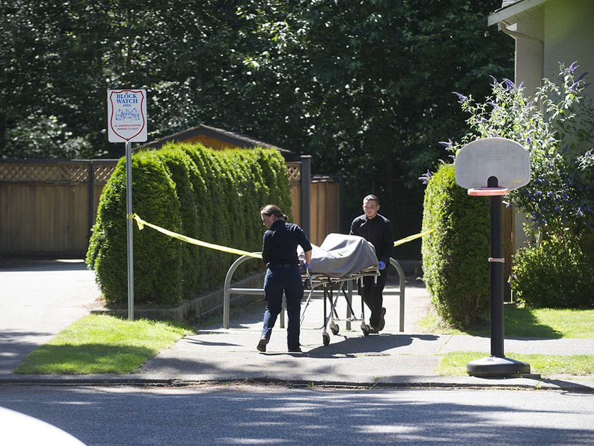 Attendants bring a body from a wooded area near 46A Avenue and 196A Street in Langley on July 15, 2020.