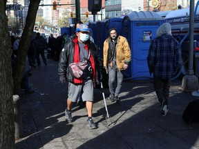 A man wearing a protective mask walks past portable toilets set up along Hastings Street following the closure of the Carnegie Community Centre back in March.