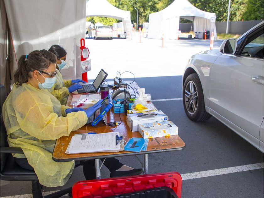 Sarah Taylor and Shruthi Nadiga conduct COVID-19 testing at a Central Park drive-thru location in Burnaby on Saturday.