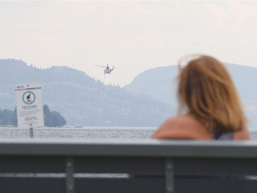 A woman on a bench at Skaha Beach watches a heli-tanker lift off from Skaha Lake en route to the nearby Christie Mountain fire.